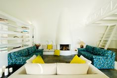 Amazing-Hotel-Livingroom-Built-Library-Cob-Fireplace-Blue-Sofas-Yellow-Tiles-VillaforRent-Oia-Santorini-Greece