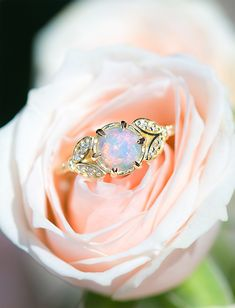 A lovely delicate ring that brings together the mystery of its Antique Style Rose Cut Opal and the sparkle of fine white Canadian mined diamonds. Delicate handset leaf shaped flourishes add a soft and classic touch, with six additional hand engraved prong set diamonds flowing down the band for that extra touch of sparkle. This ring is the perfect Opal Engagement Ring or Opal Right Hand Ring!