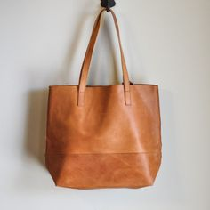 """Description: This gorgeous leather handmade tote comes in two neutral colors, Cognac and Pewter. Fit: Comfortable straps with a 12"""" drop. Includes detachable leather pouch, with snap closure. 14'' H x"""