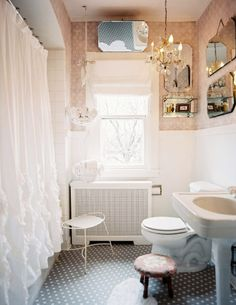 Dusky pink and white frilly bathroom with mismatched vintage mirrors, chandelier, and hanging towel basket