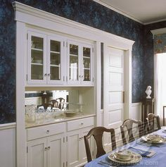 A built in china cabinet and buffet in a restored Victorian dining room, all wood is painted white, dark blue patterned wallpaper, swing door divides dining room from kitchen.