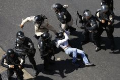 """A demonstrator is detained after jumping over a riot police line in Caracas, on February 12, 2014. (Reuters/Jorge Silva)"""