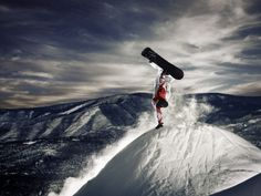 Snowboarder doing hand plant at dusk --- Image by © Brian Bailey/Corbis