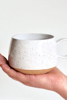 These mugs are perfect for your morning coffee, tea or hot cocoa. They are handmade on the pottery wheel using a speckled brown stoneware clay, and glazed in glossy white. A portion of the bottom of the mug is left unglazed to create a unique organic look.
