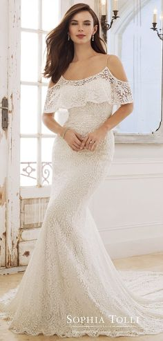 Fabulously on-trend, Rhea is a lace over stretch jersey sheath with a cold shoulder ruffled neckline, beaded spaghetti straps, princess line lace trim, a V-back finished with a zipper trimmed with diamante buttons, a scalloped lace hem and a chapel train.