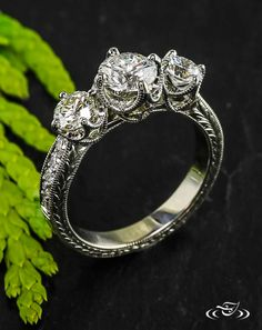 Regal Diamond Trio Engagement Ring    This regal trio of diamonds is set in a white gold 4-prong setting that is framed by filagree curls. The ring is hand engraved with a classic wheat pattern framed by a delicate milgrain border.