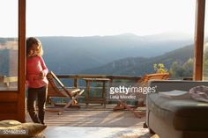 Stock Photo : Young girl leaning against patio doors to balcony