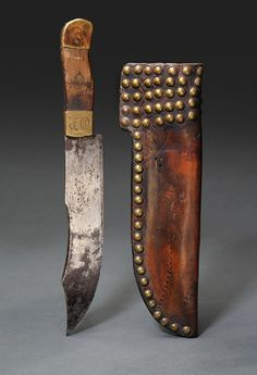 "Crow Tacked Knife Sheath with Bowie Knife.  С. 1870. The sheath is made from old saddle leather with square brass tacks. The knife is typical high quality frontier manufactured Bowie Knife. Brass buttons and Ferrule clip point blade. Engraved OE in German script.  Knife 13 1/4"". Blade 8 1/2"". Sheath 11 1/2"" x 3 3/4"". Sherwoods Spirit of America."