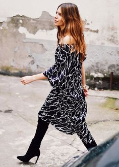 Maja Wyh in an off the shoulder printed dress and knee high boots