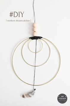 DIY Modern Dreamcatcher tutorial. I give you step-by-step instructions on how to make a dream catcher using twine, wooden beads and brass hoops. A very easy to complete DIY that anyone can finish. It's simple and elegant.