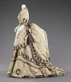 Dinner Dress 1870, American, Made of silk~~~~~The full-blown bustle silhouette had its first Victorian appearance in the late 1860s, which started as fullness in skirts moving to the back of the dress. This fullness was drawn up in ties for walking that created a fashionable puff. Accessories were petite and allowed for the focus on the large elaborate gowns.