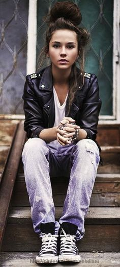 A careless look: ripped jeans, leather jacket and a messy bun.