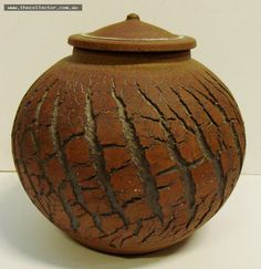 Lot 385 - Rynne Tanton postwar Australian pottery lidded pot, with crackle like design to body, signed with impressed monogram to base, 11cms tall