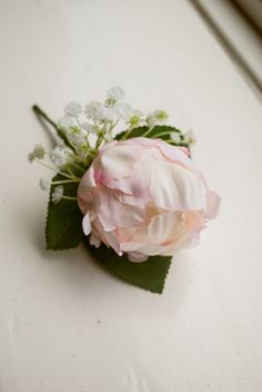 Blush pink silk wedding buttonhole / boutineer. Made from an artificial peony, a gypsophilia cluster and simple greenery. This boutonnière also