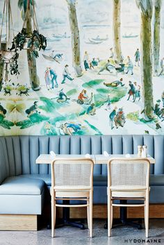 A dining room that extends to serve both as a family-friendly brunch spot and a sexy date-night spot—the carefully executed décor seamlessly transitioning from day to night includes colorful wallpaper, baby blue benches, and wooden chairs