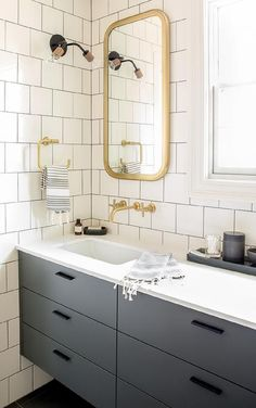 Chic gray and gold bathroom features walls clad in white square brick tiles accented with dark gray grout lined with a curved brass mirror, Restoration Hardware Astoria Flat Mirror, over a brass wall mount faucet and a gray floating washstand with dresser like drawers.