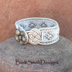The Virtuous One Here comes the bride! Wear this dressy southwest style beaded cuff bracelet either way! One side features 2 beautiful double Josephine Knots in White Metallic Leather and closes with a double loop around a silver flower button. The other side features a center row stitched in a diamond pattern of silver and white Superduo beads surrounded by white pearl seed beads and two outer rows of crystal silver-lined seed beads. Looking for something unique to wear on your special…