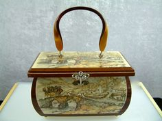 Beautiful vintage purse featuring the work of Dutch artist Anton Pieck decoupaged on the wood frame. The design is a lovely village scene with a carriage loaded with travelers. It is signed Anton Pieck in four places. Pieck is famous for nostalgic work and even designed the famous fairy tale park, Efteling, in the Netherlands.