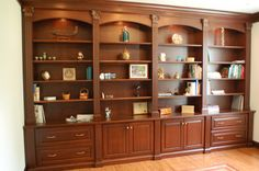 I especially love the two center sections.  The fluted vertical moulding that frames the base cabinet doors and the book case above it, the scroll sconce application at and the arches and lighting over the top shelves and capped with appropriately sized crown moulding.  This is an example of what built-ins should look like.  How to Build a Custom Bookcase | eHow.com