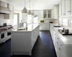 Above: Carlson sought to keep the palette simple; she used a black slate floor, which provides contrast with the statuarietto marble counters and the cabinetry painted in Blackened by Farrow & Ball. A white Caravaggio P0 pendant lighting hangs over the kitchen island.    via @Remodelista