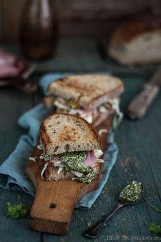 Leicht angeröstetes, dunkles Brot mit grünem Pesto und feinem Schinken - köstlich. Diese zwei Brötchen sind dekorativ auf einem schmalen Holzbrett angerichtet. Allerbeste Zutaten für Deinen Brotgenuss kannst Du online in unserem Shop bestellen: https://gegessenwirdimmer.de/