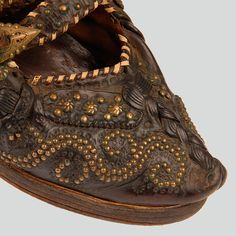 Decoration on the front of a kierpce shoe made of leather, with a sole: embossed ornaments and brass studs. Fastened with a strap. Leather cords to wrap around legs.  Podhalanian Highlanders, Zakopane-Toporowa Cyrhla, 1960s