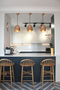Pure handleless kitchen cabinetry from John Lewis of Hungerford, here in Dove White and Blake Blue. Copper accents in the lighting and wall clock pull this scheme together, along with the oak stools and chevron floor tiles.  http://www.john-lewis.co.uk/map-showrooms/fulham/portfolio/contemporay-take-on-a-9th-floor-flat-in-north-london-john-lewis-of-hungerford