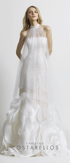 a silk organza and chantilly lace dress with a tulle cape decorated with oversized organza flowers.