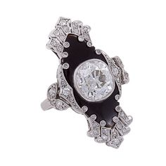 One of a kind Art Deco ring centering a large bezel-set, cushion-shaped full-cut diamond, 3.10 carats, color: I-J, clarity: VS2, surrounded by onyx and intricate platinum work set with 40 single-cut diamonds weighing approximately .42 carats. Circa 1925