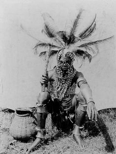 "Africa | ""The Luo; visual history"" Man heavily adorned in cowrie shell (gaagi) strips across the chest and head, coiled metal ornaments on the arm, leg and ankles (minyonge), above which are tied metal jingles, and an ostrich-feather headdress (kondo udo). He also holds a wooden club. He has a dagger (pand ligangla) hanging from a strap across his chest and a number of split hippo teeth (lak rao) ornamenting his head. 
