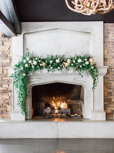 A gorgeous cascading fireplace mantel floral arrangement with mixed greenery including Italian ruscus and eucalyptus and white blooms of roses and lisianthus. Photo: Stephanie Couture Photography Venue: The Lake House Calgary spring wedding Wedding Fireplace Decorations, Wedding Mantle, Aisle Decorations, Wedding Flower Arrangements, Floral Arrangements, Wedding Centerpieces, Farmhouse Fireplace Mantels, Unused Fireplace, White Fireplace