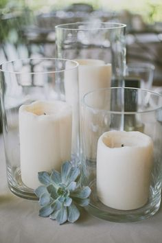 A trio of LED pillar candles in vases with pale green succulents tucked in between; surrounded by varied heights of silver mercury glass LED votives STEMS Floral Design