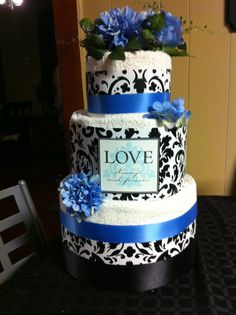 Towel cake made for a bridal shower. Made from rolled towels wrapped with wrapping paper, wide ribbon, and decorated with artificial flowers. Use toilet paper rolls for a filler so you don't have to use as many towels. Everyone can use toilet paper & towels! Great shower gift