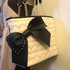 Betsy Johnson Tote Cream and black tote, with big black bow with gold studs detail, absolutely classic and cute. Has partial gold plated link to the strap. Body is 100% polyurethane, lining is 100% polyester. Cool graffiti sayings inside tote. Brand new never used. Betsey Johnson Bags Totes