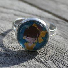 Zilverkleurige ring met meisje met gele strik.