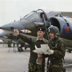 A warrant officer of the Army Intelligence Corps discusses operational photo-intelligence with a pilot of No 1 Squadron RAF, in front of a row of Harrier aircraft at Royal Air Force Wittering, Northamptonshire. Air Force Aircraft, Fighter Aircraft, Military Jets, Military Aircraft, Air Fighter, Fighter Jets, Airplane History, British Airline, War Jet