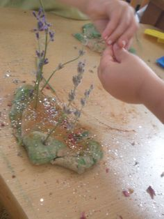 Children make aromatherapy playdough by adding essential oils and dried herbs.