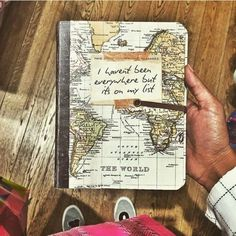 ▷ 1001 + Ideas for Adventure Journal Designs for Your Inner Traveler Travel diary, a brown hand holding a notebook, with a yellow and green world map on the front page, shoes, wooden boards