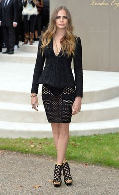 Though she might have been absent from New York Fashion Week, model and newly minted actress Cara Delevingne made her appearance at London Fashion Week in standout style. Arriving at the Burberry Prorsum show in London today, the beauty showcased some skin in a black blazer-like top and sheer geometric print skirt with matching cage heels. The neon yellow-green trim lining her peep-toe heels was the only color she needed in her chic black ensemble. With shiny, flowing locks and pretty…
