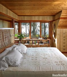 "In a house outside of Seattle, for an air of calm seclusion, ""almost everything in the master bedroom is hushed,"" designer Markham Roberts explains. He hung an antique Persian camel saddlebag above an Edelman suede bolster at the head of the built-in platform bed. An antique textile from Jordan acts as a coverlet.   - HouseBeautiful.com"