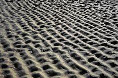 Op deze afbeelding zie je het beeldaspect ritme want je ziet allemaal kleine zandhoopjes die even groot zijn.