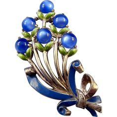 Scrumptious blue moonglow plastic cabochons grace this splendid Coro floral bouquet, all done up with blue and green enameling, and tied up in a bow  $77