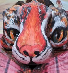 Three models with their bodies painted form a 3D image of a tigerPicture: ZUMA / Rex Features