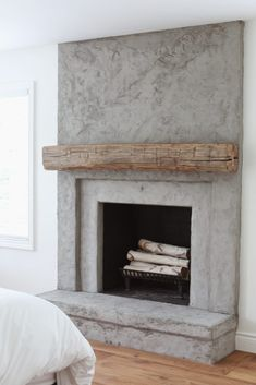 concrete fireplace with reclaimed wood mantel from real antique wood - lindsay marcella design Stucco Fireplace, Concrete Fireplace, Bedroom Fireplace, Farmhouse Fireplace, Fireplace Hearth, Home Fireplace, Fireplace Remodel, Fireplace Surrounds, Fireplace Design