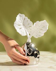 Com a flor de porcelana esculpida à mão, o difusor em frasco de vidro metálico é uma verdadeira obra de arte. Em dourado, prata ou branco, é uma peça autoral e exclusiva feita em nosso ateliê para criar experiências sensoriais encantadoras em sua casa. #difusor #difusordeporcelana #decor #homedecor #perfumaria #taniabulhoes #costeladeadao Perfume, Fragrances, Mason Jars, Diffuser, Silver, Flower, Porcelain Ceramics, Fragrance