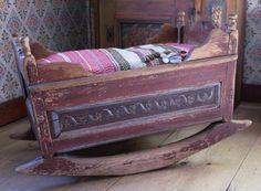 Finely bedded's rustic cradle from Sunnansjö in Dalarna who have kept their original painting. - Fint bäddad är allmogevaggan från Sunnansjö i Dalarna som fått behålla sin originalmålning.