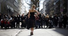 A guest poses for photographers in the street before Dolce & Gabbana's Autumn/Winter 2015/16 collection during Milan Fashion Week on March 1, 2015.