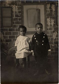 African American children: Descriptions: Two unidentified African American children posing in front of brick and wisteria backdrop.     Vintage African American photography courtesy of Black History Album, The Way We Were.