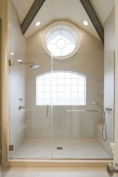 There was really no help needed in making this shower look large — it already is! But tiling all the way up to the pitched ceiling was still a smart choice. It doesn't force a break at the wall and it draws your eye all the way up to the circular window and beautiful beams