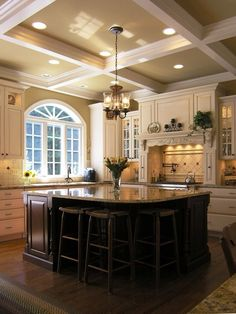 Like the antique white cabinets with the dark island. Nice lighting too.
